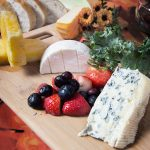 assortment of cheeses and berries on a wooden board