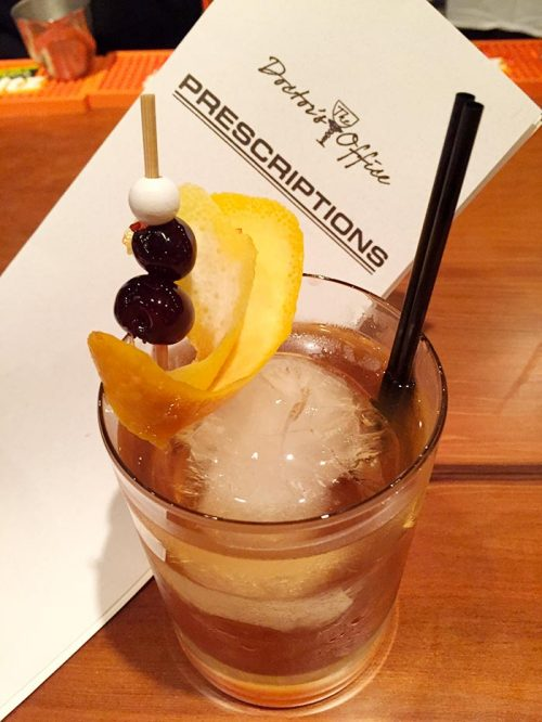burbon cocktail with cherry and lemon rind garnish