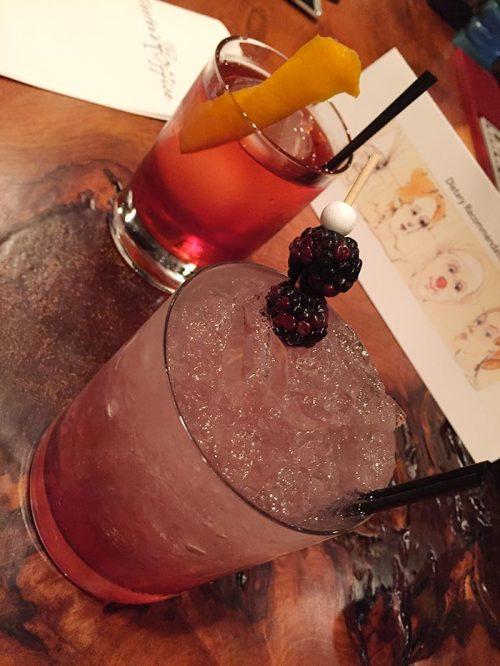 pink mixed rum drink with blackberries as garnish