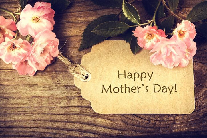 happy mothers day written on a card with flowers