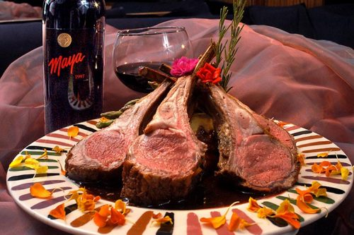 short ribs on a plate with a glass of red wine and flowers on plate