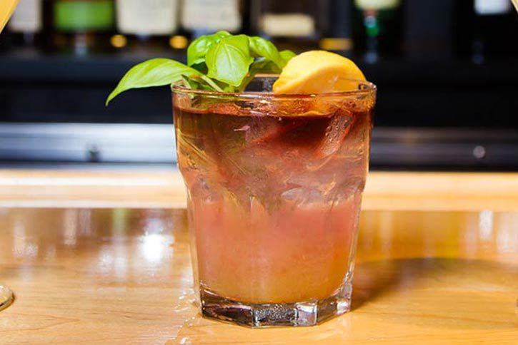 pink mixed drink with basil leaf and lemon garnish