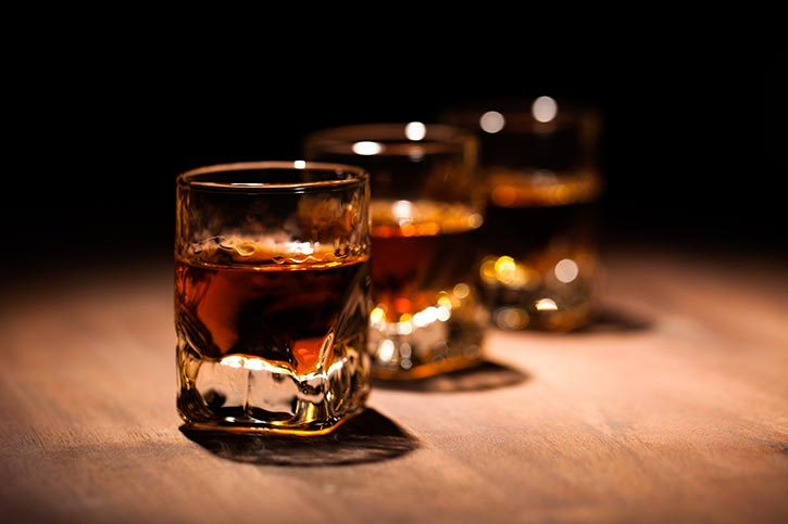 line of whiskey shots on a dark table