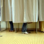 People voting behind a curtain all you see is their shoes
