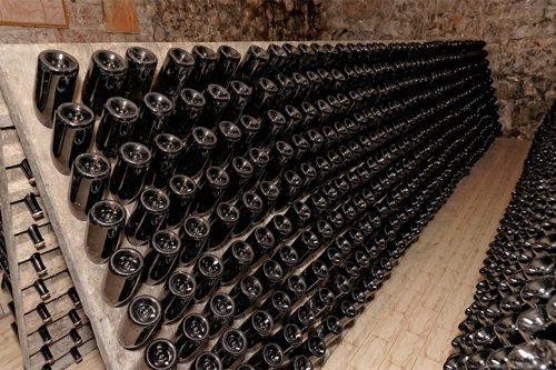 Many red wine bottles stacked in a cellar