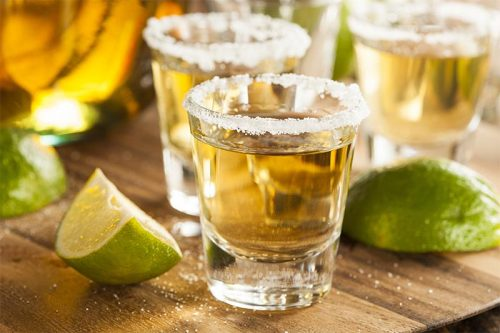 Tequilla shots with salt on the rim of shot glasses and limes