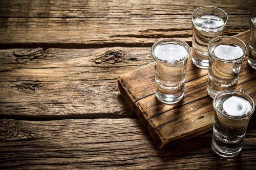 shots of vodka on a wooden table